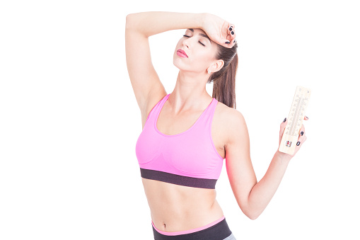 Woman at gym holding thermometer like summer heat