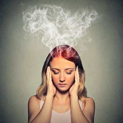 Stressed woman thinking steam coming out up of head