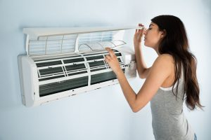 Woman checking on air conditioner